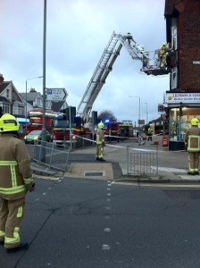 Firefighters make a wind-damaged cast iron drainpipe safe