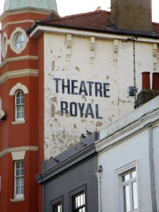 Flaking paint peeling off the wall proclaiming the Theatre Royal in New Road