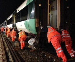 Rail workers right a derailed train at Brighton