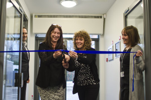 Bilingual Primary School founder and chair of governors Marina Gutierrez cuts a ribbon at entrance of the school's new premises, helped by teaching assistant Katherine Davies and watched by fellow founding governor Javier Ruiz and head teacher Wendy King