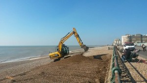 Diggers move the shingle down the beach now the winter storms have passed - by Emma Moore