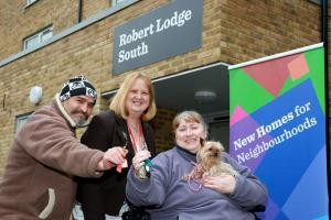 Councillor Anne Meadows welcomes new Robert Lodge residents Tekin Akkurt, left, and Sylviane Cayrol, with her dog Tilly