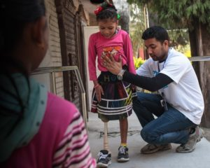 Handicap International physiotherapist Sudan helps eight-year-old Nirmala adapt to her prosthetic leg after the earthquake in Nepal