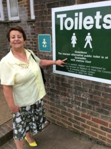Councillor Dawn Barnett outside the public toilets in Greenleas. The sign directs people to those at the Grenadier shops, which are also to close