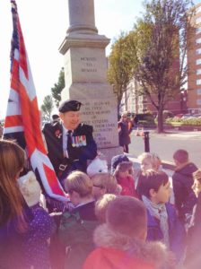 Royal British Legion standard bearer Mick O'Keefe with children from St Andrew's CE Primary School in Hove